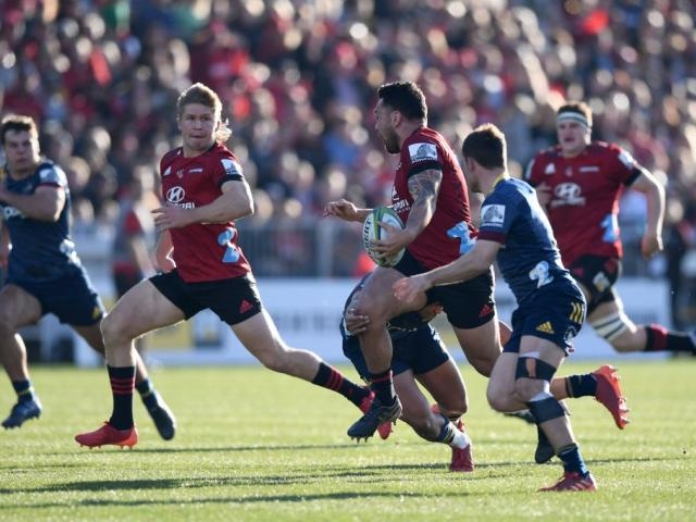 Richie Mo'unga offloads to Jack Goodhue in the Crusaders' win over the Highlanders in...