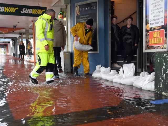 Dave Mitchell (right) and Tony Vaas sandbag shops in Mosgiel during a November 2018 flood. PHOTO:...