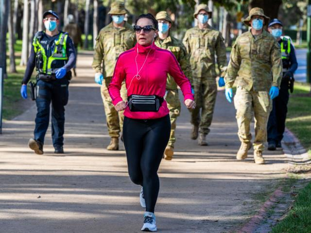 A woman jogs near Australian Defence personnel and protective service officers as they patrol in...
