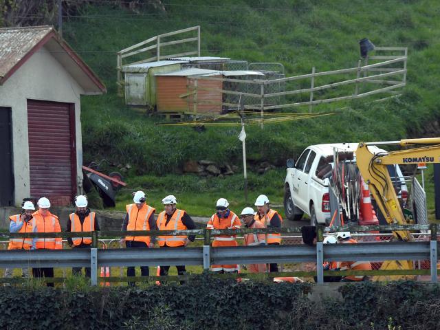A team of workmen inspect the slumped culvert above Moller Park, Ravensbourne, on SH88 between...