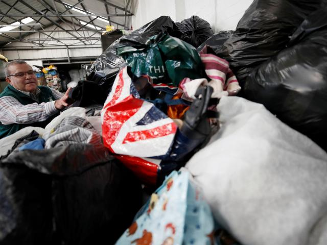 Antonio de Carvalho from Green World Recycling sorts through bags of clothing at the company's...