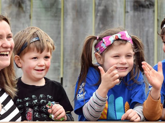 St Kilda Kindergarten teacher Jess Anderson uses sign language to communicate with (from left)...