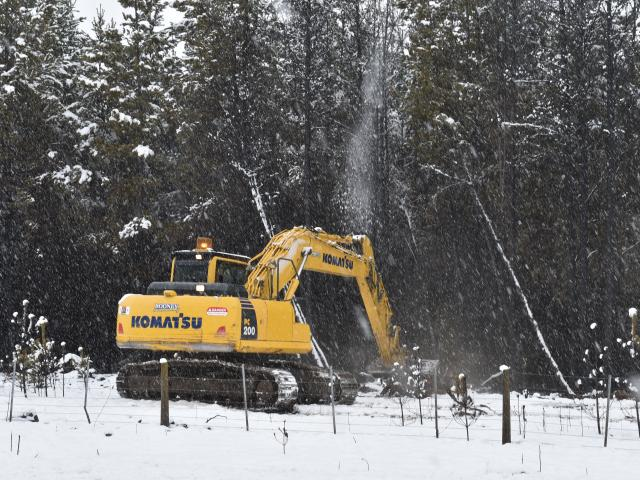 A digger works In the snow to dislodge hot spots amongst trees at the Pukaki fire on Tuesday...