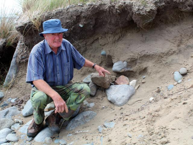 Beachcomber Alan Clark, of Greenhills, points to the pile of rocks which now covers the spot...