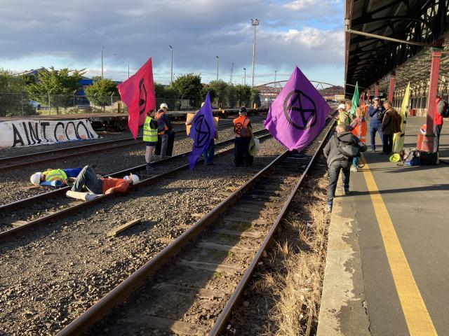Activists against coal mining lay on the tracks at the Dunedin Railway Station this morning....