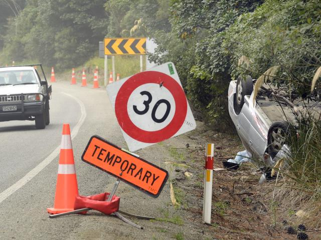 A crashed car rests on its roof on the Northern Motorway following a crash yesterday morning....