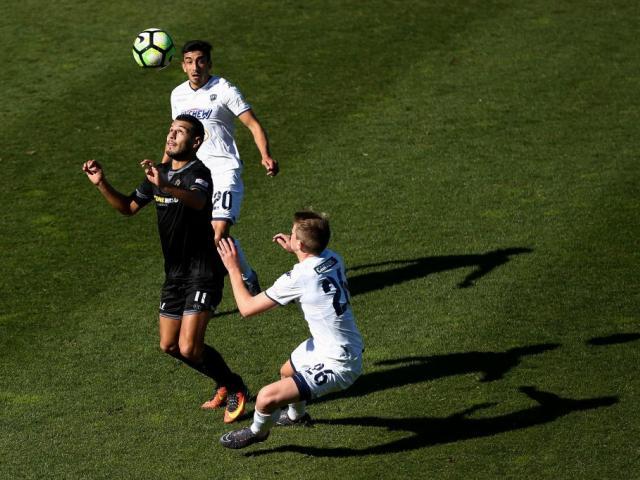 Mario Barcia of Team Wellington controls the ball under pressure from Callum McCowatt and...