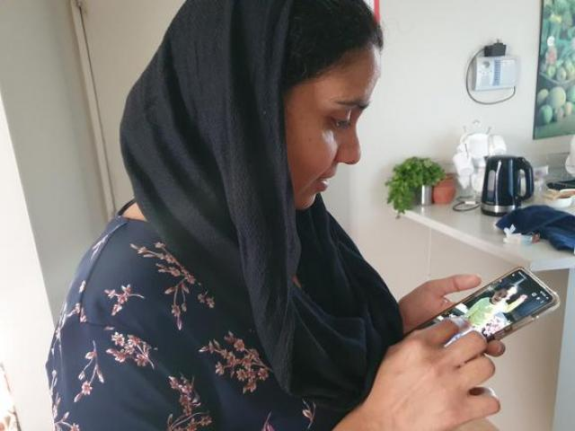 Gagandeep Kaur looking at a photo of her daughter, Nimrat, who is still in India. Photo: Katy...