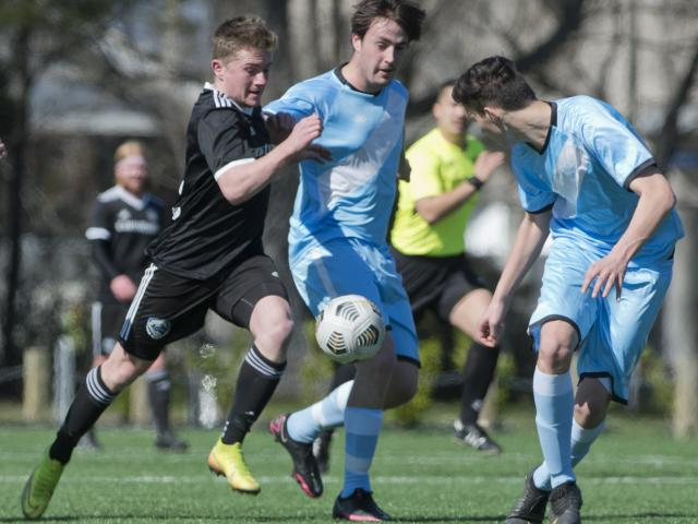 Coastal Spirit player Cameron Bean looks for a way past Oliver Cassidy (centre), of South City...