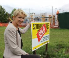 Real estate agent Rebecca Ireland crouches beside a recently sold section in Omakau. Photos by Jono Edwards.