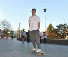 First-year marketing student Harry Webby (18) skates past the Clocktower on his way to a lecture...