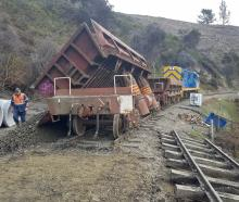A wagon dumps fill for repairs on the railway line.