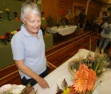 Jane Pheasant, of Dunedin, admires the floral arrangements. Photos: Alexia Johnston