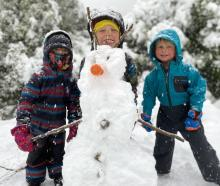 Edie (5) and Torben (7) Clark and Archie Brown (5) show off their snowman in Closeburn,...