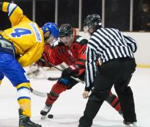 Stampede player Matt Schneider (left) and Red Devils player Jaxson Lane duel for the puck in a...