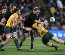 Owen Franks gets a pass away as he is caught by the Wallabies defence. Photo Getty