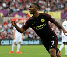 Manchester City's Raheem Sterling celebrates scoring their third goal against Swansea. Photo...