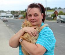 Tossie Liebenberg, of Balclutha, hugs one of her cats  tightly after it was rescued from a house...