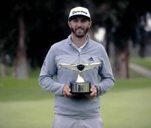 Dustin Johnson celebrates his victory following the final round of the Genesis Open golf...