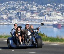 Andrew Sim drives his new 350 Chev-powered trike up Highcliff Rd with (from left) Rachel Horrell ...
