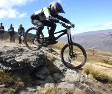 Queenstown downhill mountain biker Sam Robbie (17) hits a rock jump during his run at the...