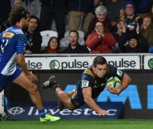 Highlanders flanker Dillon Hunt dives over to score  in front of Stormers winger Dillyn Leyds...