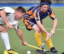 Fighting for the ball in premier club hockey at the McMillan Hockey Centre on Saturday are...