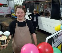 Salvation Army alternative education student Wayde Fryer (15) serves coffee, watched by education...