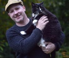 Jesse Bering holds his cat Tommy, who has lived with him in the United States, the United Kingdom...