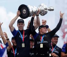 Team New Zealand skipper Peter Burling celebrates with skipper Glenn Ashby as they hold the...