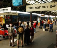 People gather to see the Southerner leave Dunedin Railway Station for the last time in 2002....