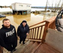 Henley residents Hamish and Emma McGregor stand clear of the floodwater which has inundated their...
