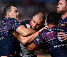 Simon Mannering of the Warriors is tackled by Te Maire Martin and Kane Linnett of the Cowboys....