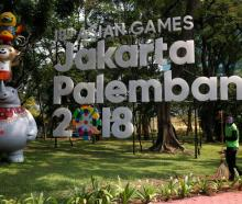 A worker cleans near a sign for the upcoming 2018 Asian Games, in Jakarta. Photo: Reuters