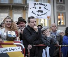 An Iranian Woman in traditional bavarian dress stands in front of protesters at Chancellor Angela...