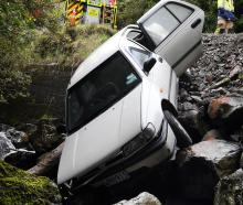 Emergency services personnel prepare to remove a stolen car which was dumped in the Water of...