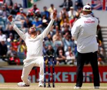 Australia's Nathan Lyon celebrates after dismissing England's Moeen Ali during the fifth day of...