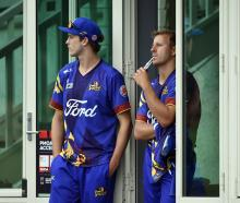 Otago players Warren Barnes (left) and Neil Wagner shelter from the rain as they wait in vain for...