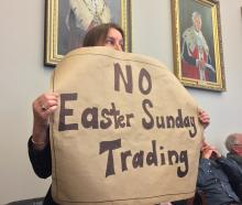 Margaret Wilkinson holds up a sign during the Dunedin City Council's debate on allowing Easter...