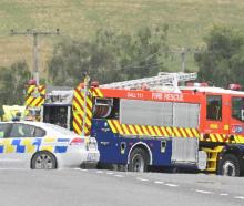 Emergency services work at the scene of a collision between a van and a truck on State Highway 1,...