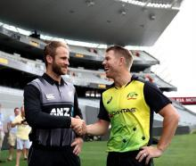 Kane Williamson and David Warner shake hands at yesterday's media session at Eden Park. Photo:...