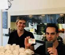 Isaac Forsyth (right) holds a re-usable cup the Good Earth cafe suggests people use instead of a...