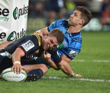 Highlanders second five-eighth Tei Walden, in the tackle of Blues winger Matt Duffie, grounds the...