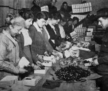 Women and Australian troops packing Red Cross parcels at a bonded warehouse in the Old Bailey,...