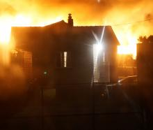 A view past houses in Dart St, Oamaru, of a fire in Regina Lane about 5am yesterday. Photo:...