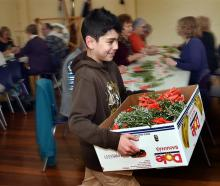 Cobie Smith (9) gathers the posies created in the HMNZS Toroa Dunedin naval reserve headquarters...