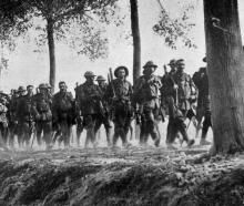 A tired battalion coming out of the firing line for a rest near Ypres on the Western Front. -...