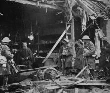 An elderly shopkeeper sits in his wrecked premises hoping to pick up trade as troops pass by. —...