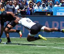 Dylan Collier dots down to score for New Zealand as Fiji's Semi Kunatani attempts a tackle. Photo...