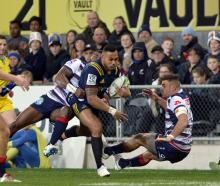 Tevita Li, of the Highlanders, fends off Tom English, of the Rebels, during the round 19 Super...